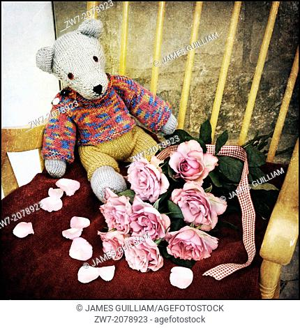 Childs hand crafted Teddy bear with bouquet of pink coloured Roses, textured image