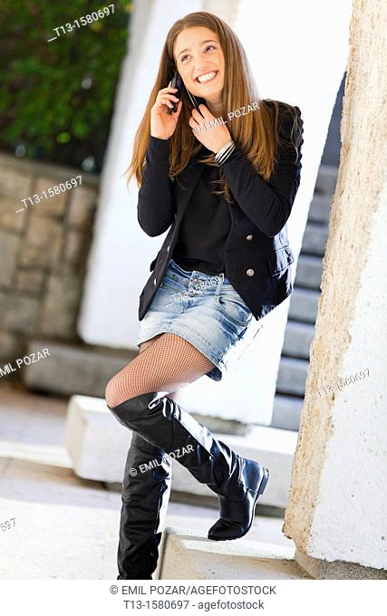 Attractive young woman is using a cellular phone