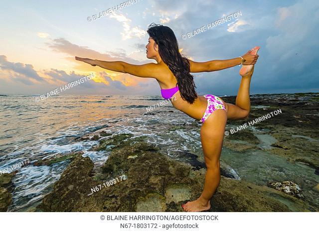A woman at sunrise doing yoga along the Caribbean Sea at Akumal, Riviera Maya, Mexico