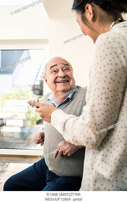 Senior man smiling at nurse with stethoscope at home