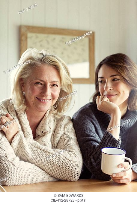 Portrait smiling mother and daughter in sweaters drinking coffee
