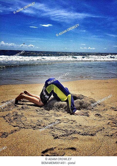 Boy sticking head in sand at beach