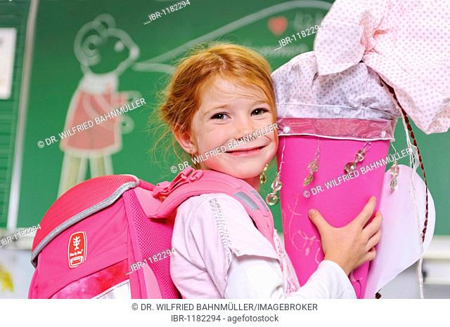 Girl on her first day at school holding a schultuete, school cone filled with sweets and gifts