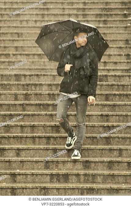 young man, Afghan ethnicity, standing outdoors with umbrella on stairs during winter, snowing, in Munich, Germany