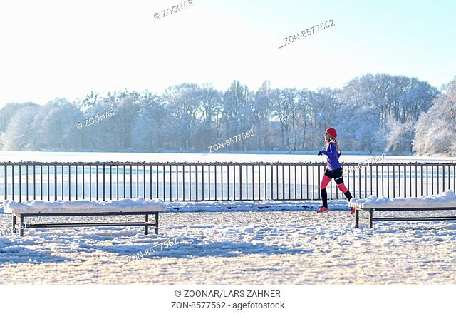 Young woman running in winter snow along a promenade overlooking the ocean as she enjoys the invigorating cold weather in a healthy active lifestyle concept