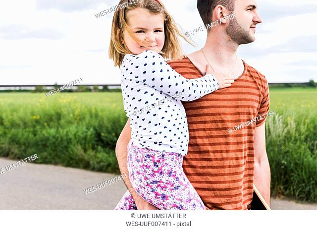 Father holding daughter outdoors