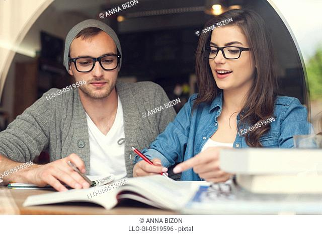 Hipster young couple studying together at cafe. Krakow, Poland
