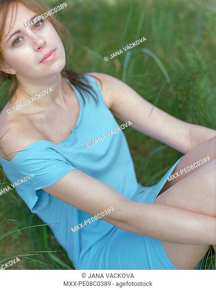 Woman sitting in grass, looking at camera