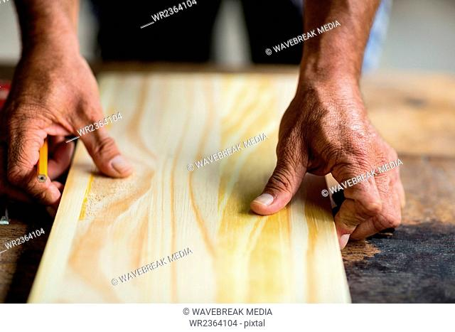 Carpenter hands measuring wooden plank