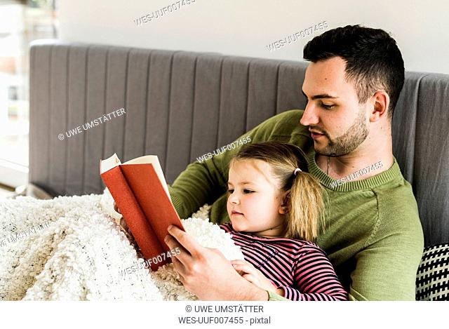 Father and daughter reading a book at home