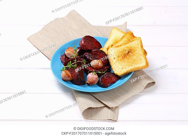 plate of baked beetroot and garlic with toasted bread on beige place mat