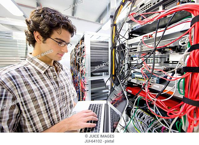 Technician working on laptop computer in Server room of data center