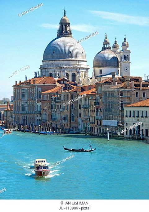 Water taxi boats and gondola on sunny Grand Canal in front of Santa Maria della Salute and architectural buildings in Venice, Italy