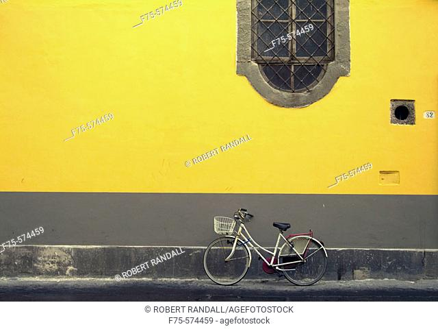 Bike leaning against a yellow wall in Lucca, Italy