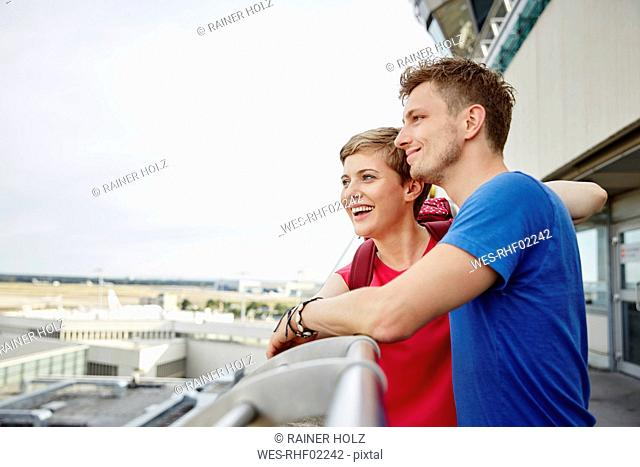 Happy couple on observation deck at the airport