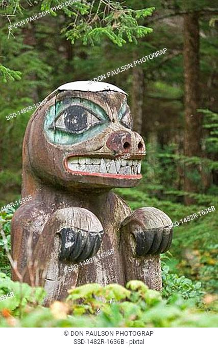 Totem poles of a bear in a forest, Kasaan Totem Park, Tongass National Forest, Alaska, USA