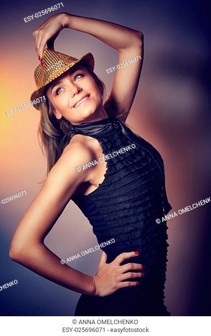 Beautiful dancer girl wearing stylish dress and shiny hat over dark background, disco dancing, enjoying time in night club