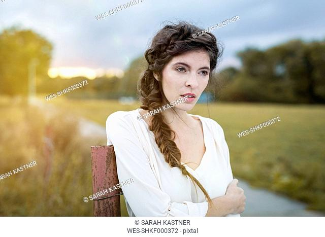 Portrait of woman with braid leaning against pole at twilight