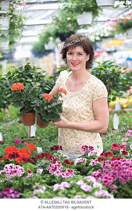 Woman with geranium in a greenhouse