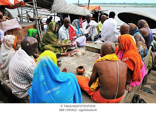 Pilgrims praying at ghat by the Ganges river