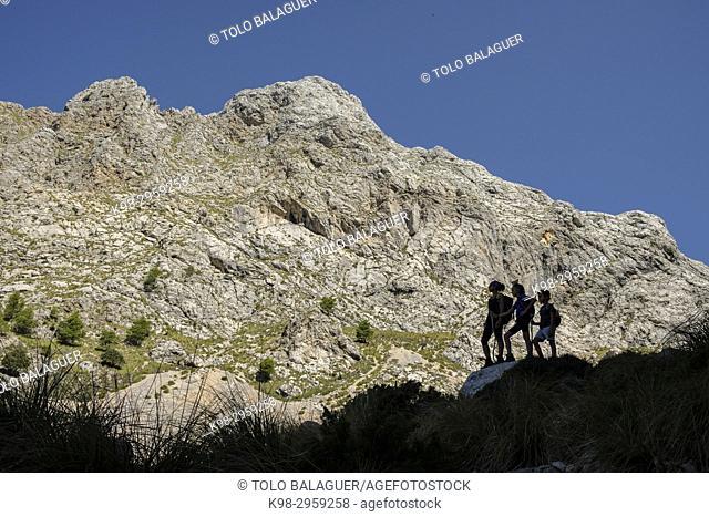 Silhouettes of hikers in Coma de n'Arbona, Penyal des Migdia, 1401 metres, término municipal de Fornalutx, paraje natural de la Sierra de Tramuntana, Mallorca