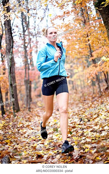 Woman Running On Dirt Trail In The Fall