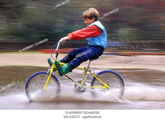 portrait,park-scene, boy, 10 years, is driving with high lifted legs with his yellow BMX-bike through a puddle  - 0, GERMANY, 22/10/2002