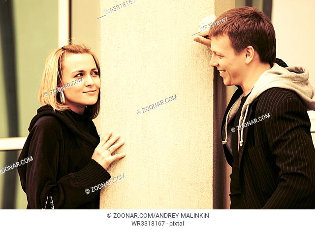 Happy young fashion couple flirting on city street