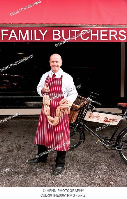 Butcher holding sausage outside shop