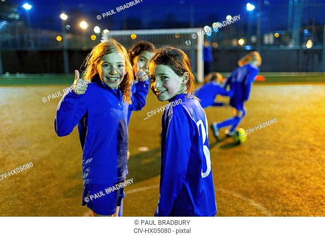 Portrait confident girl playing soccer, gesturing thumbs-up