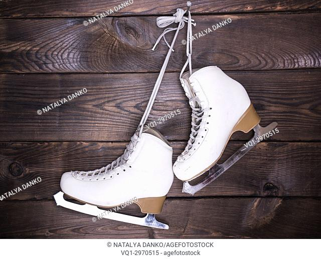 women's white used leather skates hang on a nail on a brown wooden background