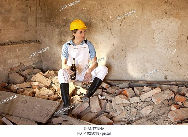 A female construction worker sitting on rubble holding a beer