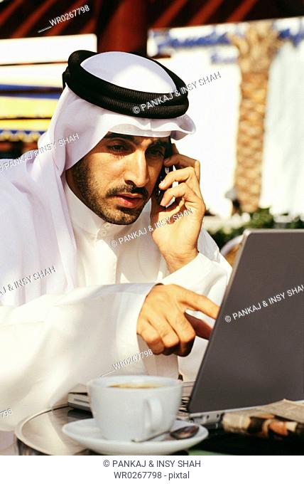 An Arab man is focused at his laptop as he converses on the mobile phone