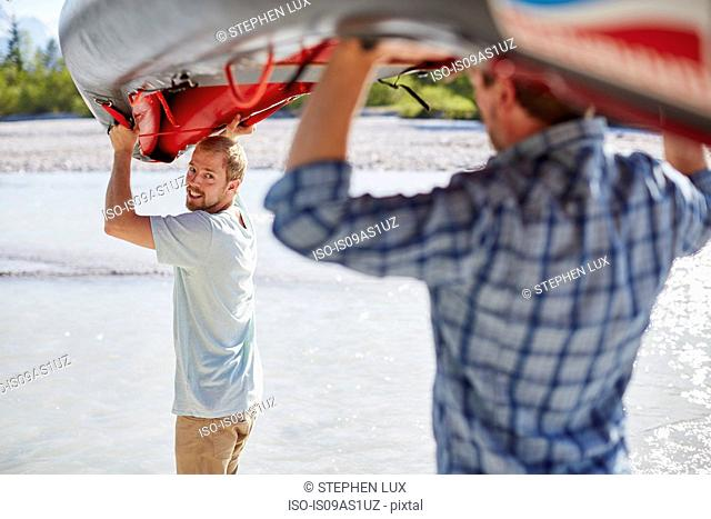 Rear view of two men carrying dinghy above their heads to water