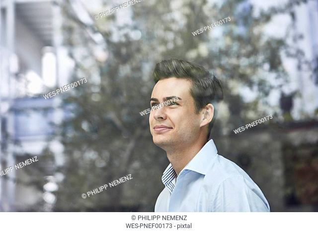 Portrait of smiling young businessman looking out of window