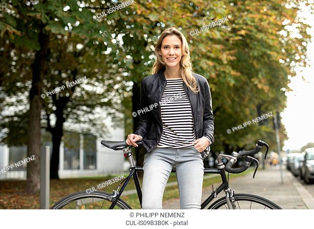 Portrait of mid adult woman leaning against bicycle in city park