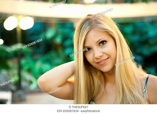 Smiling young attractive woman under warm tungsten lighting
