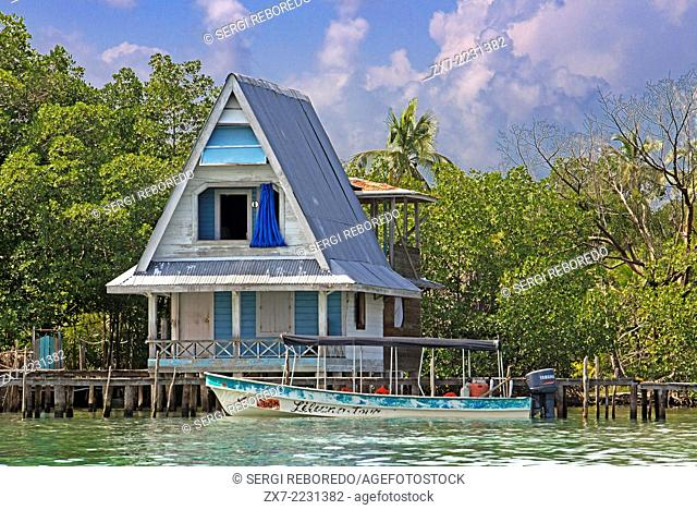 House on stilts over water with solar panels and dense tropical vegetation in background, Bocas del Toro, Caribbean sea, Panama