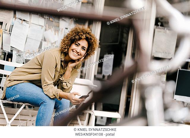 Woman in front of coffee shop, holding smart phone