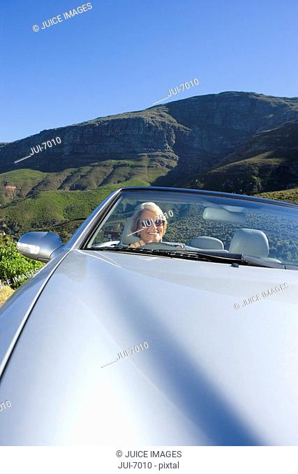 South Africa, Western Cape, senior woman driving silver convertible car along mountain road, smiling, front view, portrait tilt