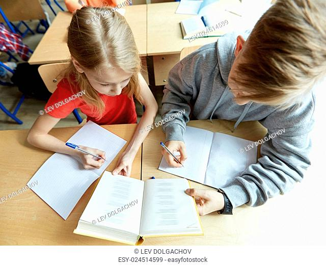 education, high school, learning and people concept - students with book writing to notebooks on lesson
