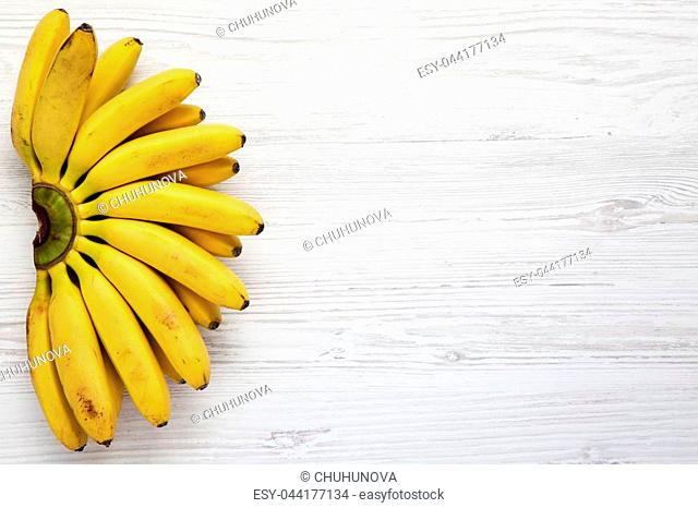 Baby bananas on white wooden background, from above. Top view. Copy space