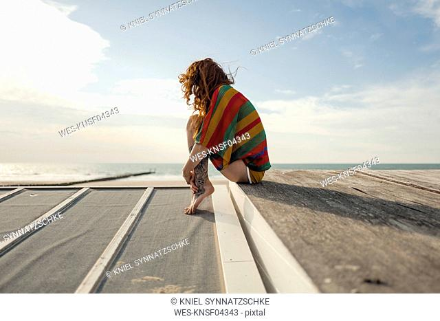 Woman with tattoo crouching on plank, looking at the sea