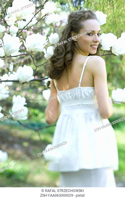 Young woman standing next to flowering tree, smiling over shoulder at camera