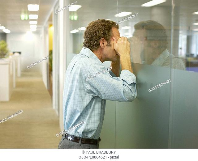 Businessman peering into conference room