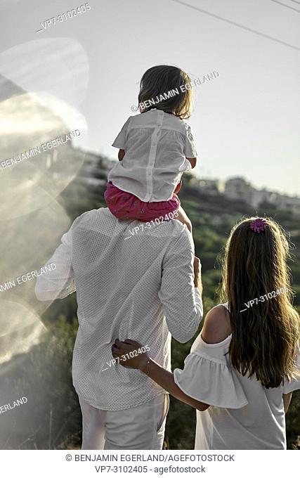 back of family outdoors. Parenthood, enjoying togetherness, bonding, trip. In holiday destination Chersonissos, Crete, Greece