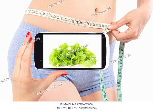 Weightloss and diet in information age. Diet, detox and fitness app on smartphone screen and attractive beautiful woman measuring her body with tape measure