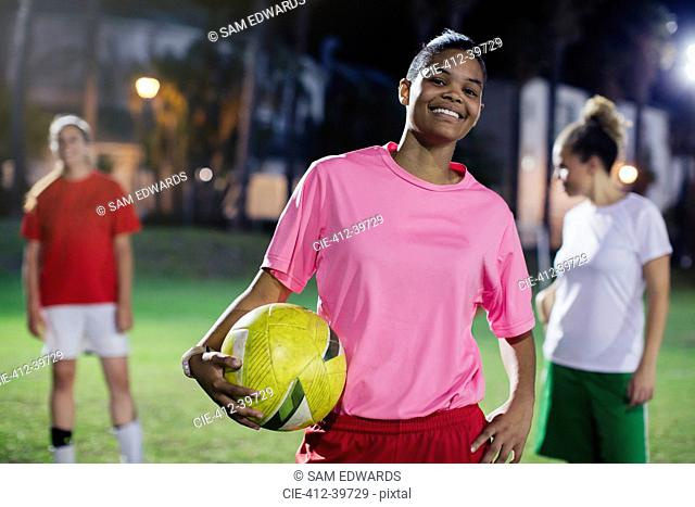 Portrait confident, smiling young female soccer player with ball on field at night