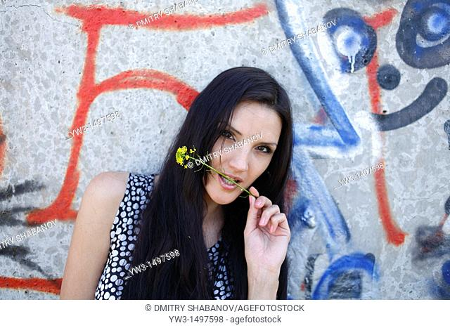 25 year old woman outdoors against graffiti with wild flower in the mouth