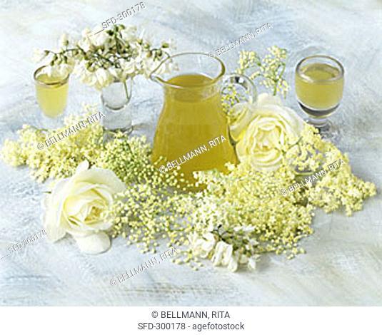 Elderflower drink in a carafe beside elderflowers and roses